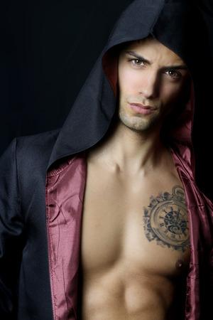 modelos hombres: Hombre muscular hermoso con una capucha negro Foto de archivo