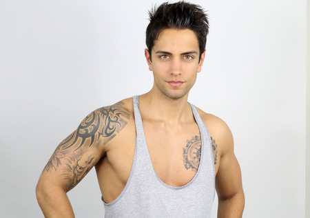 handsome tattooed athletic man on a white background