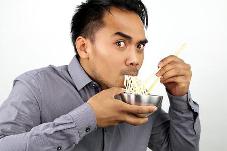 eating noodles: Asian man eating noodles