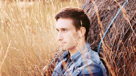 champ de mais: homme assis dans un champ de maïs Banque d'images