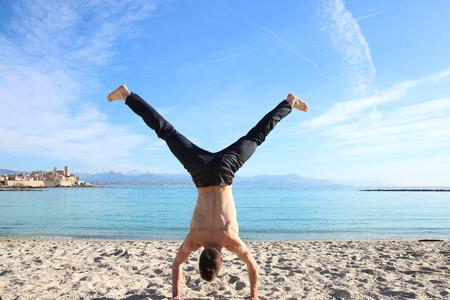 handstand: man doing handstand on the beach