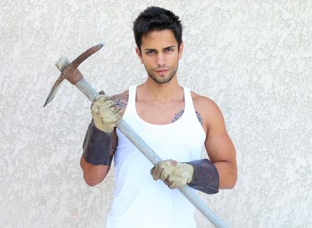 handsome gardener holding a pickaxe photo