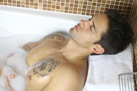 modelos hombres: hombre atractivo que miente en un baño Foto de archivo