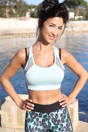 ropa deportiva: hermosa morena en ropa deportiva en primera línea de playa