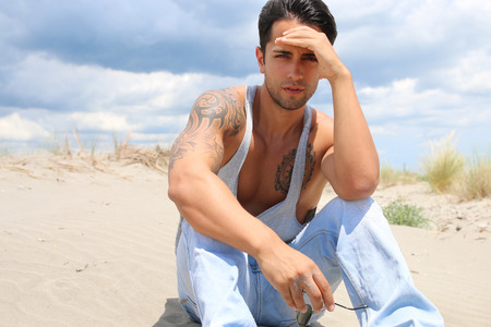handsome man sitting on the sand