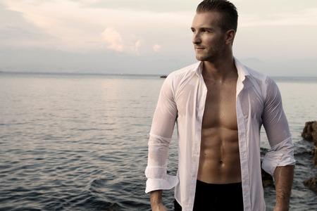 해변 옆에있는 젊은 남자