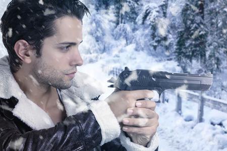 male killer: handsome guy holding a gun