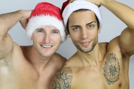 modelo desnuda: dos hombres sexy vistiendo un sombrero de santa Foto de archivo