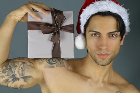 modelos hombres: sexy santa claus - hombre sosteniendo un regalo de Navidad