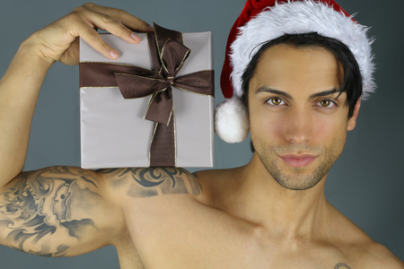 model male: sexy santa claus - man holding a christmas present