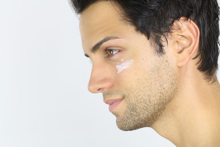 moisturizer: Close portrait of a man with her face moisturizer is