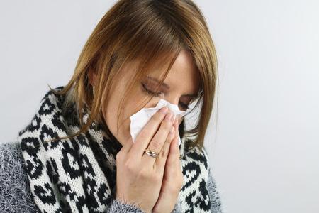personne malade: femme blonde se mouchant