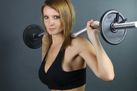 girl squatting: young woman doing weight training