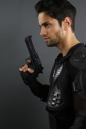 cops: super cops - handsome man posing with a gun Stock Photo