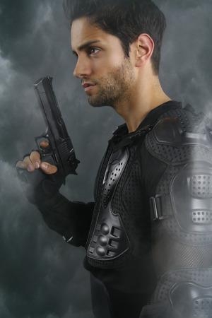 handsome guy: handsome man holing a gun