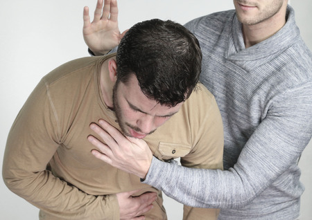 choking: Heimlich - first aid gesture over a white background