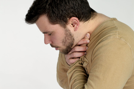 choking: first aid - young man choking over a white background