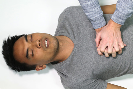 cardiopulmonary: first aid - a man doing CPR over a white background
