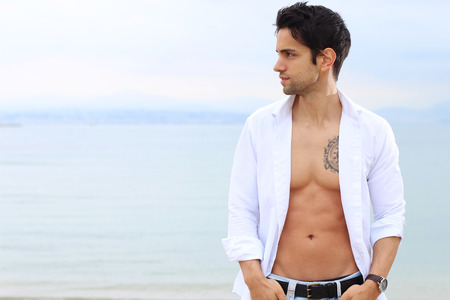 open shirt: handsome male with an open shirt near the sea Stock Photo