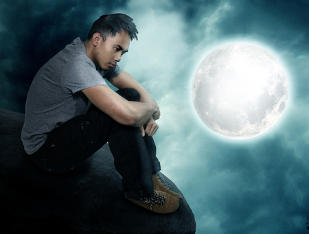 dreamer: young man sitting at a full moon