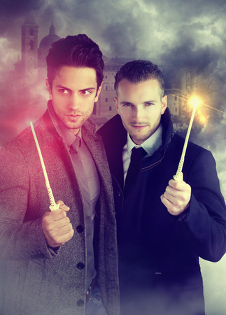 wizards: two young wizards holding a magic wand