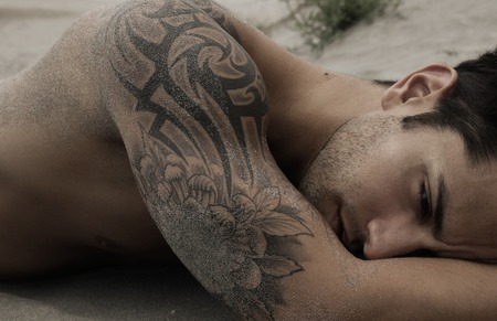 Handsome male lying on the sand Stock Photo