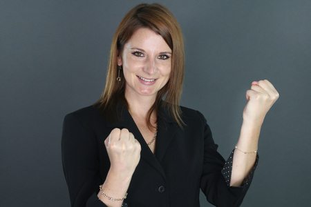 clenching fists: happy young woman clenching fists His Stock Photo