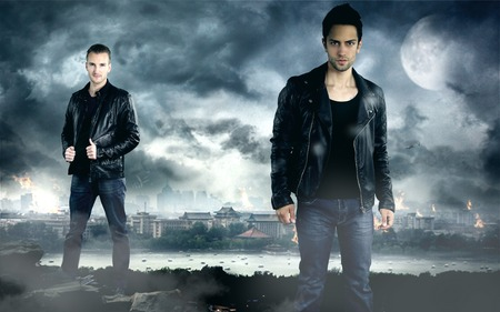 two handsome men posing in front of the dark city