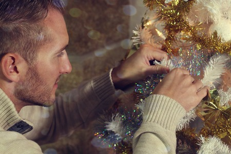 decorating christmas tree: Young man decorating a Christmas tree Stock Photo