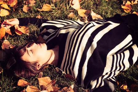 lying on leaves: Beautiful woman lying in autumns leaves Stock Photo