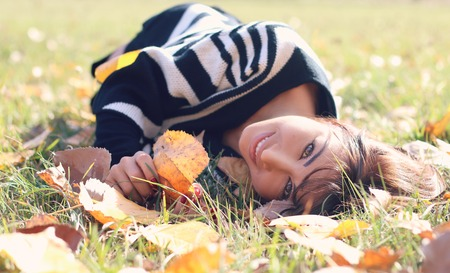 lying on leaves: Beautiful girl lying in autumn leaves