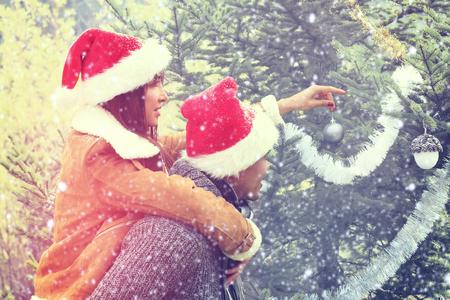 decorating christmas tree: Happy Couple Outdoor Decorating Christmas Tree