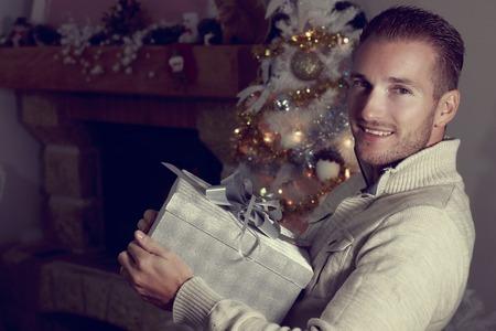 Jeune homme blonde tenant un cadeau de Noël
