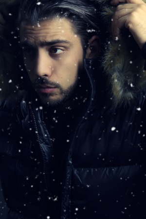 fur hood: Handsome man holding a fur hood next to a snowfall Stock Photo