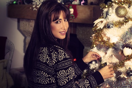 decorating: Beautiful young woman decorating a Christmas tree