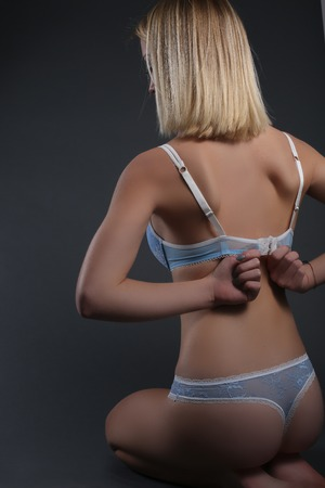 erotical: young female ass with blue lingerie on gray background