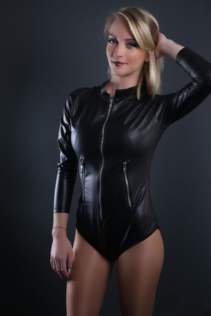 Fashion woman wearing a leather suit on a gray background