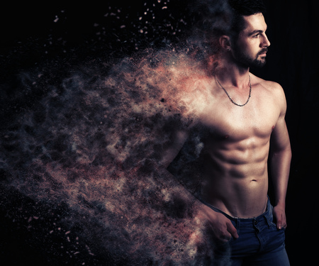 Sexy male creating an explosion of particles