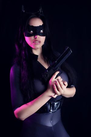 Beautiful girl wearing a catsuit holding a gun Stock Photo