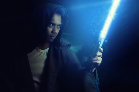 Young warrior holding a lightsaber on a dark background