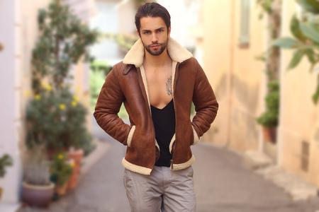 Openluchtdalingsportret van de modieuze knappe mens die het jasje van het manierbont dragen.