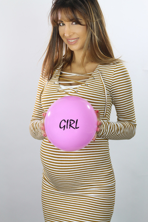 Beautiful pregnant woman announcing the baby gender with a pink balloon