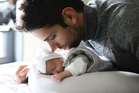 Proud father kissing his newborn baby daughter