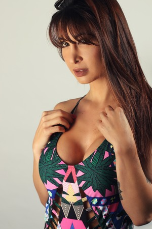 Gorgeous woman wearing one piece bikini on a gray background