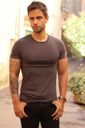 handsome male model wearing gray t-shirt in casual urban style