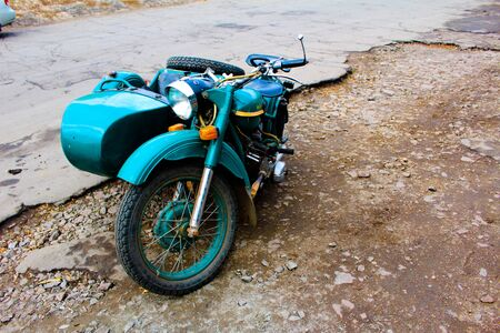 Old soviet motorcycle stands on the side of the road