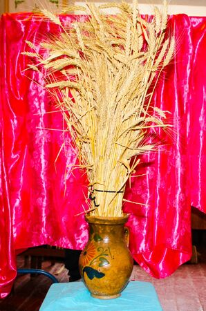 A pot with ears of wheat on a table is shot from the side.