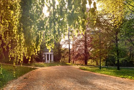 Stadtpark mit Bäumen, Morgensonne und einem kleinen Tempel in Linz Standard-Bild - 100752312