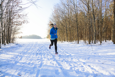 femal: Femal in winter while jogging in snow with trees in background Stock Photo