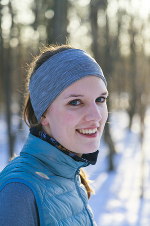femal: Femal in winter portrait after jogging in snow with trees in background